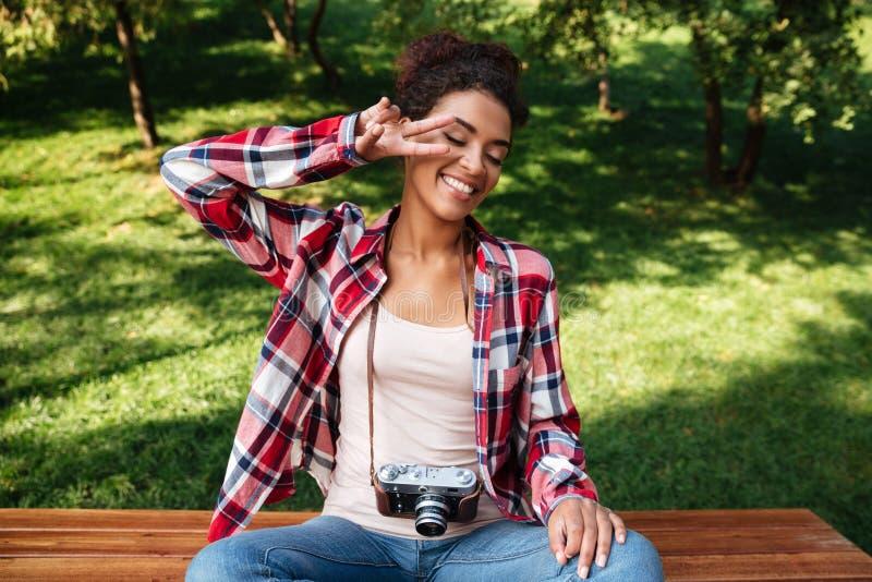 De zitting van de vrouwenfotograaf in openlucht in park stock foto