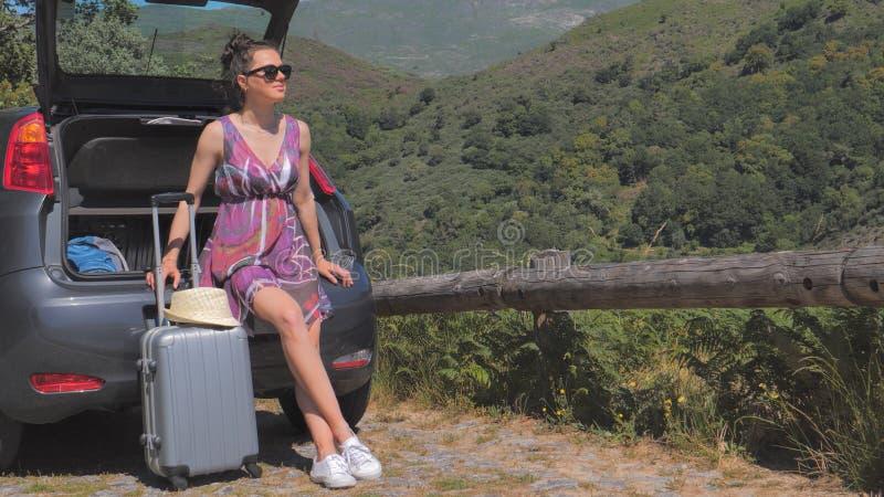De zitting van de vrouwenreiziger op vijfdeursautoauto openlucht stock afbeelding