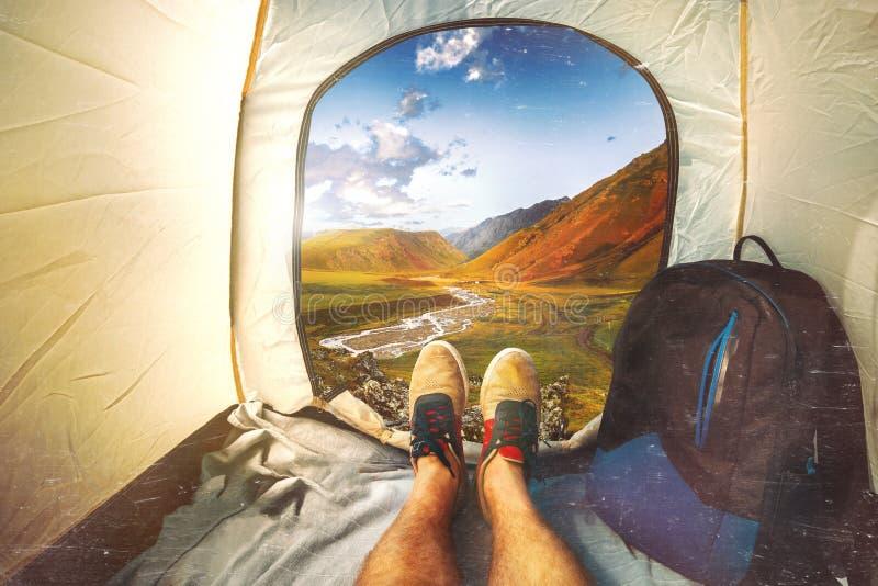 De Zitting van de wandelaarmens in een Toeristentent door Mountain View met Krassen Het concept van de vakantievakantie r Standpu stock afbeeldingen