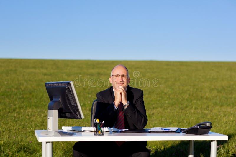 De Zitting van zakenmanwith hands clasped bij Bureau op Gebied royalty-vrije stock foto's