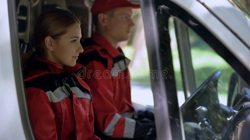 De zitting van de ziekenwagenbemanning in vervoer, professionele medische hulp bij noodgevallen royalty-vrije stock afbeelding