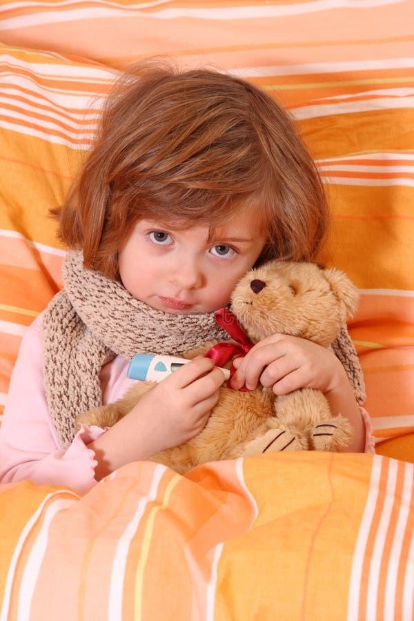 De zittingszieken van het meisje in bed stock afbeeldingen
