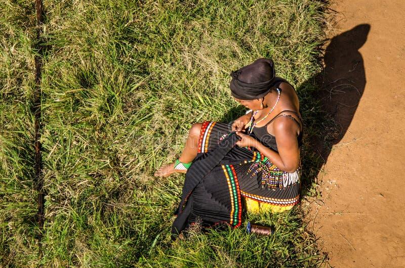 De Zoeloes vrouw gekleed in traditioneel toestel naait haar traditionele kleding Zuid-Afrika, Afrikaanse levensstijl stock fotografie