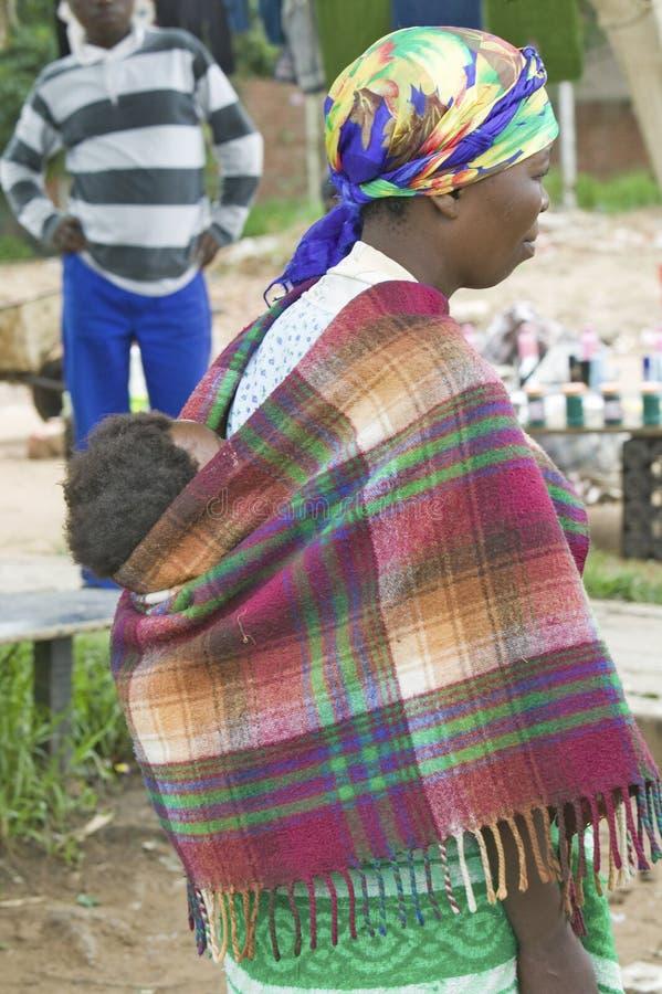 De Zoeloes vrouw met kind op haar kleedde zich terug in helder gekleurde kleding, Zoeloeland, Zuid-Afrika stock fotografie