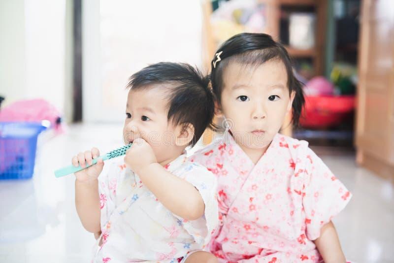 De zoete Aziatische kleine kinderen genieten van thuis samen speel stock foto