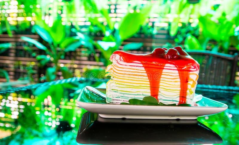De zoete cake van de regenboogrouwband met het bovenste laagje van de aardbeisaus op plaat op de lijst en schaduw groene boomacht stock afbeeldingen