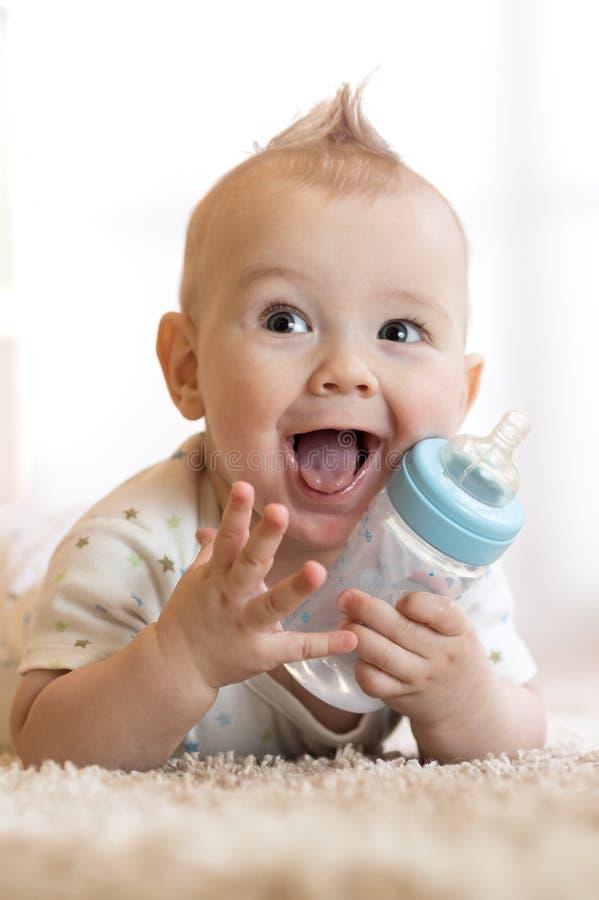 De zoete fles van de babyholding met water en het glimlachen stock afbeeldingen