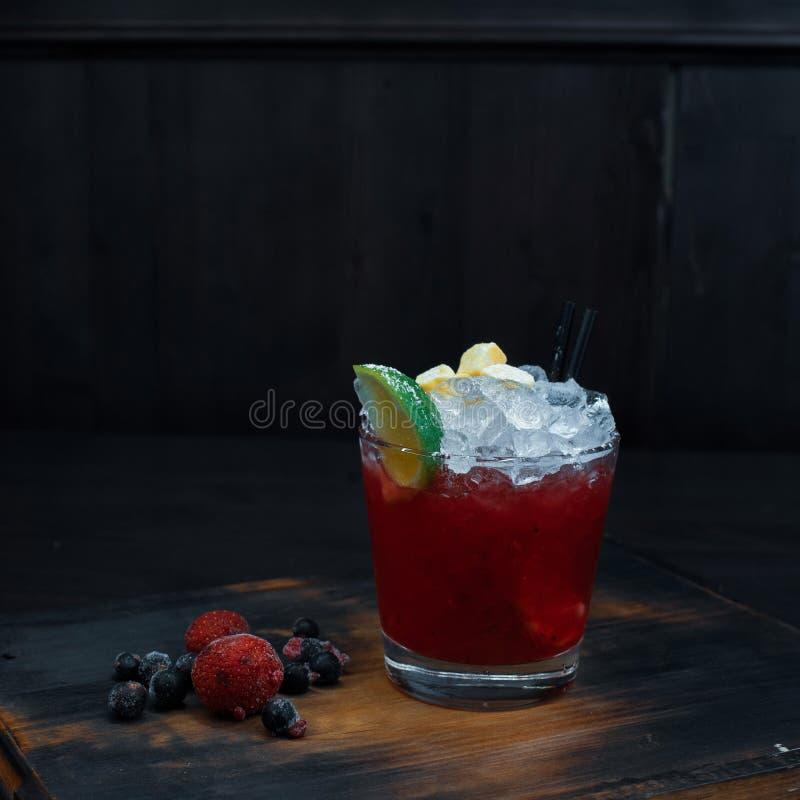 De zoete koude alcoholische cocktail van rode kleur met verse bessen en kalkplakken bevindt zich op een houten lijst in een bar royalty-vrije stock afbeeldingen