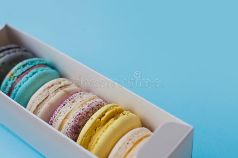 De zoete macaroni van de giftdoos op een blauwe achtergrond stock fotografie