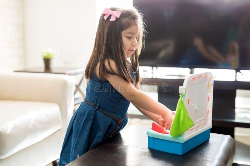 De zoete meisjeswas dient stuk speelgoed gootsteen in royalty-vrije stock foto's