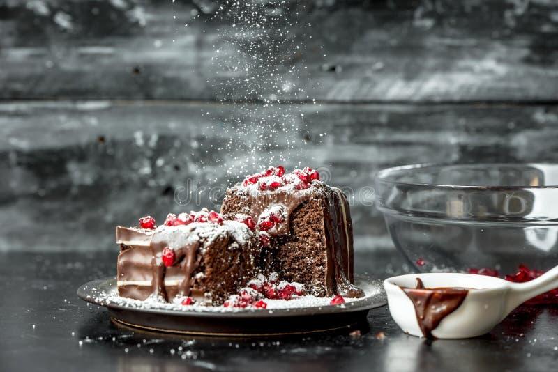 De zoete ogenblikken - zoete ogenblikken - brownies goten hete, vloeibare die chocolade, met rode granaatappelzaden en gepoederde stock fotografie