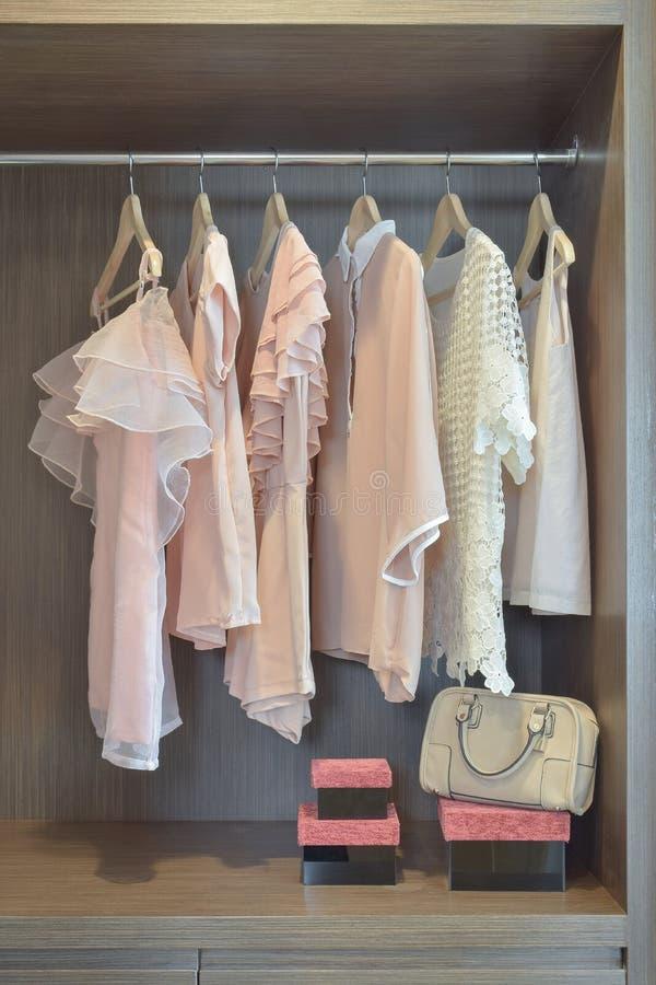 De zoete pastelkleurblouses hangen in open garderobe stock foto's