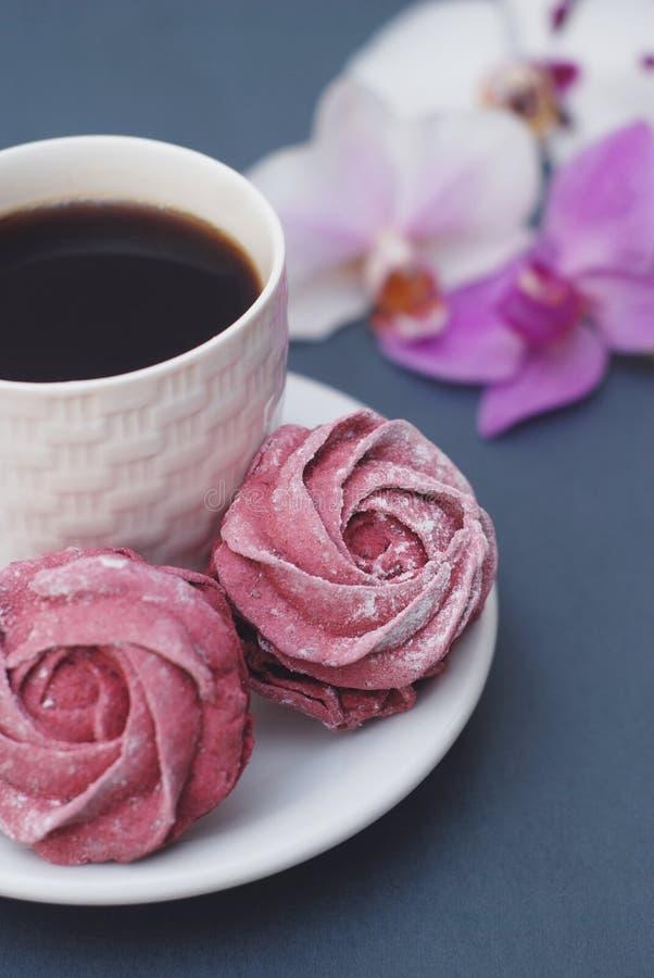 De zoete Roze Schuimgebakjes en de Kop van Koffie op Blauwe Grijze achtergrond met Orchidee bloeien De lenteachtergrond met exemp stock afbeeldingen