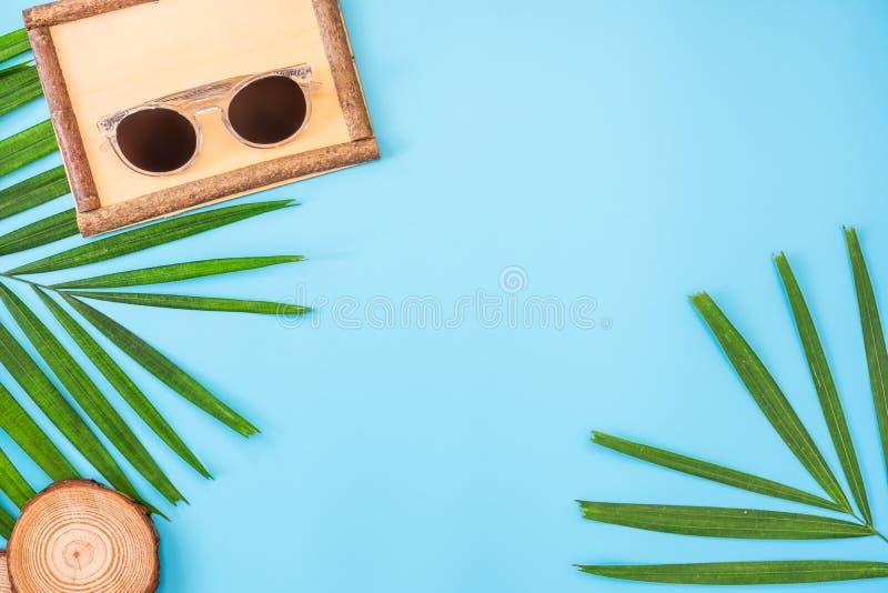 De zomer blauwe banner met houten beeld grame, zonnebril, zeeschelp en palmblad op blauwe hoogste mening als achtergrond royalty-vrije stock foto