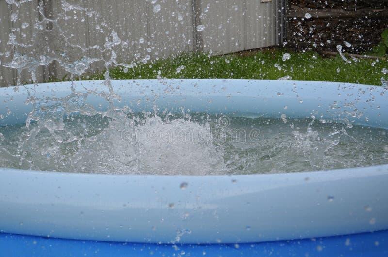 De zomer is een hete dag Blauwe die pool met water wordt gevuld De plonsen van het water Het dorp is uit stad Rust, vakantie stock afbeeldingen
