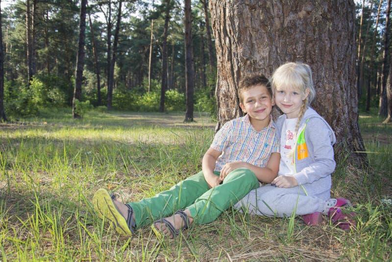 De zomer is een zonnige dag weinig gelukkige jongen en het meisje zit unde royalty-vrije stock foto's
