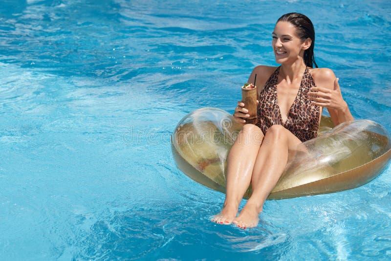 De zomer en recreatieconcept Aantrekkelijke vrouwenzitting op grote rubberring in midden die van zwembad, cocktail in hand houden royalty-vrije stock foto's