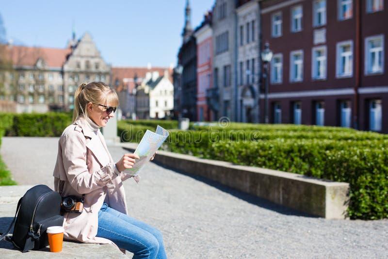 De zomer en reisconcept - vrouw in zonnebril met kaart, rugzak en camera in oude stad van Tallinn, Estland stock afbeelding