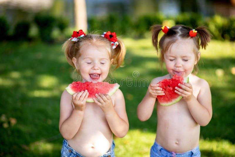 De zomer gezond voedsel gelukkig glimlachend kind twee die watermeloen in park eten Close-upportret van leuke meisjes royalty-vrije stock afbeeldingen