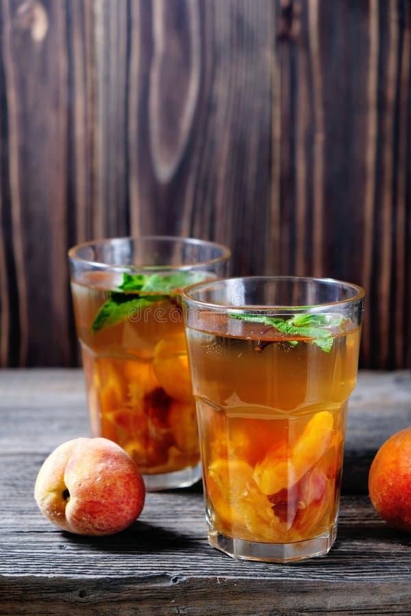 De zomer koude dranken: eigengemaakte perziksangria met ijsblokjes, en munt in glas op houten achtergrond royalty-vrije stock fotografie
