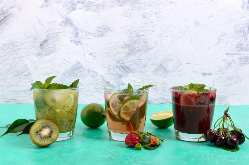 De zomer koude dranken met verse vruchten, bessen en munt stock afbeeldingen