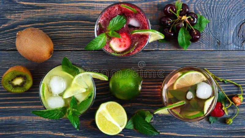 De zomer koude dranken met verse vruchten, bessen en munt stock foto's