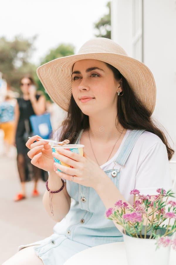 De zomer Mooie jonge vrouwenzitting in een koffie en het eten van roomijs royalty-vrije stock foto