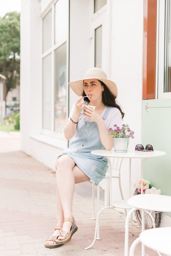 De zomer Mooie jonge vrouwenzitting in een straatkoffie en een smakenroomijs Blauwe hemel, kalme wateren stock foto's