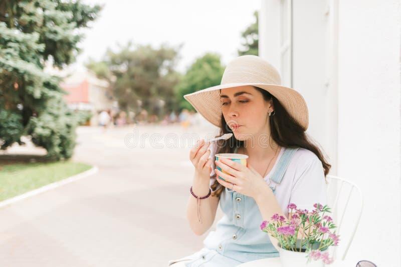 De zomer Mooie jonge vrouwenzitting in een straatkoffie en een smakenroomijs De ruimte van het exemplaar royalty-vrije stock afbeeldingen