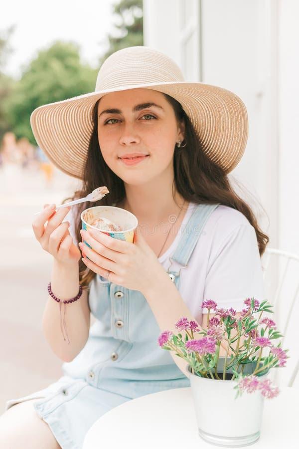 De zomer Mooie jonge vrouwenzitting en het glimlachen in de zomerkoffie en etend roomijs royalty-vrije stock afbeelding