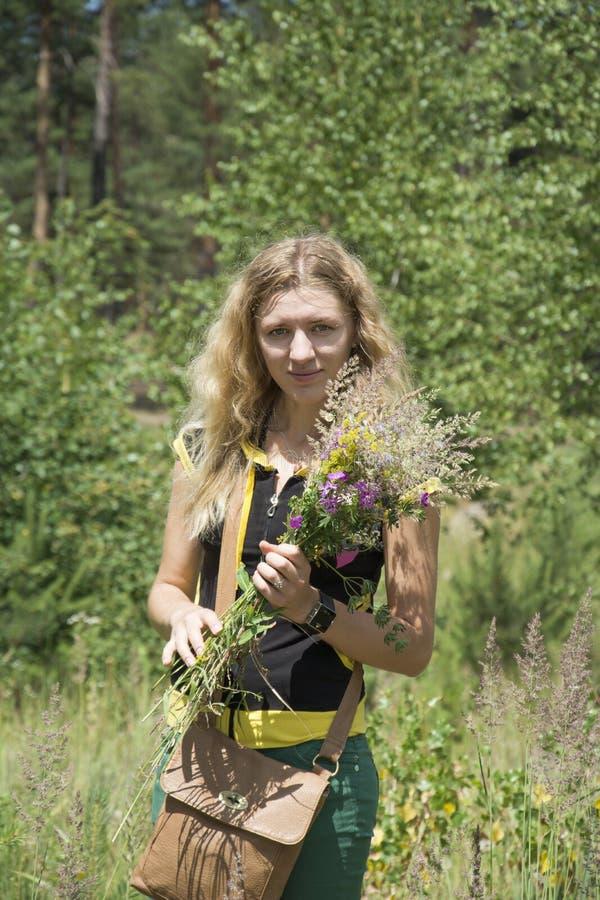 In de zomer op het gazon houdt het meisje een boeket van wildflower stock afbeeldingen