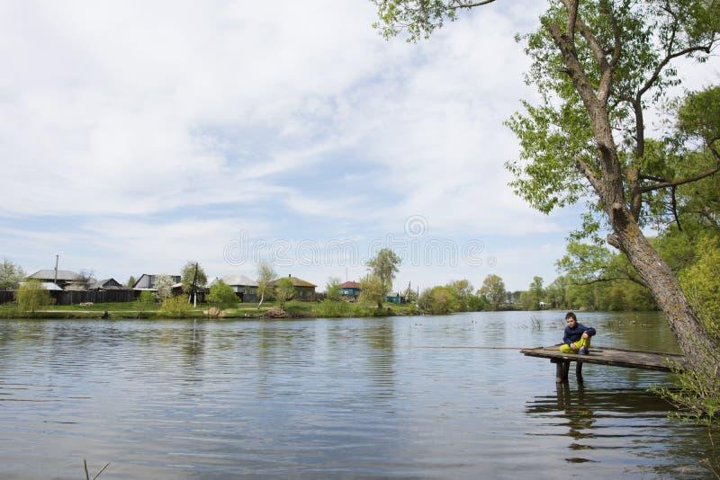 In de zomer op het meer dichtbij de dorpsjongen die vissen, royalty-vrije stock afbeeldingen
