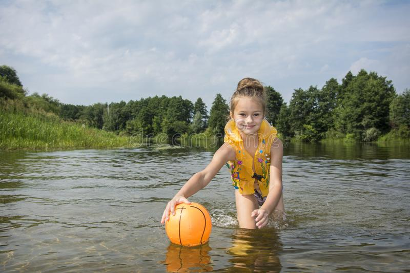 In de zomer, op de rivier, speelt een meisje in een vest met een bal royalty-vrije stock afbeelding