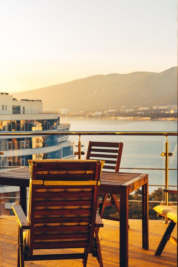 De zomer Openluchtbalkon met Tuinmeubilair in Overzees en Zonsondergangoverzicht Van de de Toevluchtrecreatie van penthouseflats  stock afbeelding