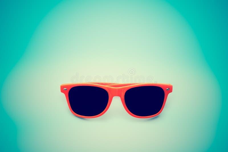 De zomer oranje die zonnebril op vignetting blauwe achtergrond wordt geïsoleerd Minimaal conceptenbeeld voor zonbescherming royalty-vrije stock foto