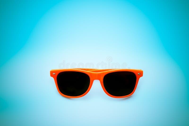 De zomer oranje zonnebril op vignetting blauwe achtergrond Minimaal conceptenbeeld voor zonbescherming royalty-vrije stock afbeeldingen