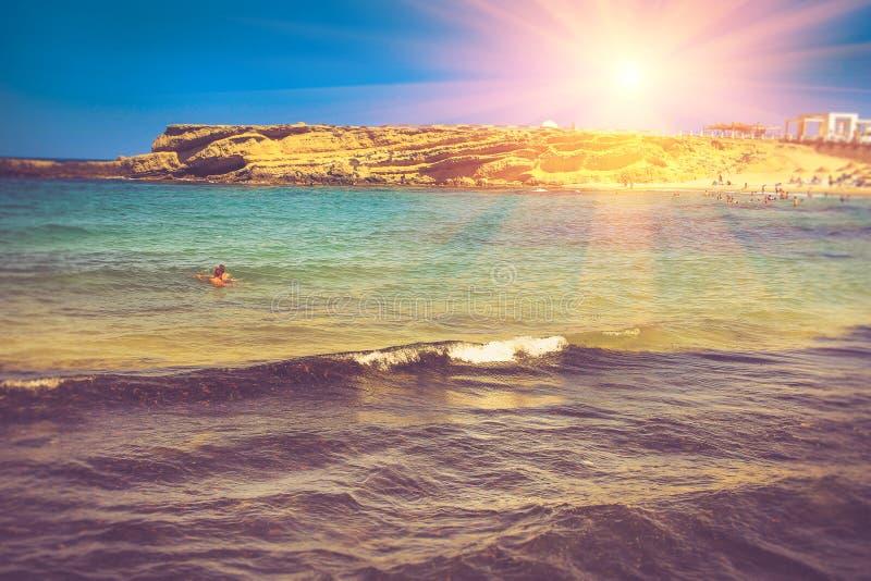De zomer overzees landschap, rotsachtige strand en zwemmers bij zonneschijn royalty-vrije stock foto's