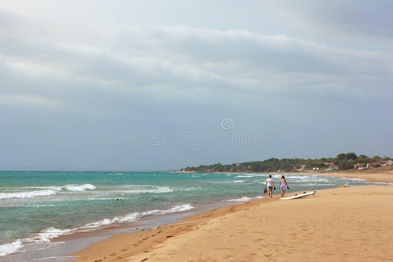 De zomer overzees menings zandig strand, golven in zonnige dag Fonkelende golven die op het strand omwikkelen Twee tieners lopen  royalty-vrije stock foto's
