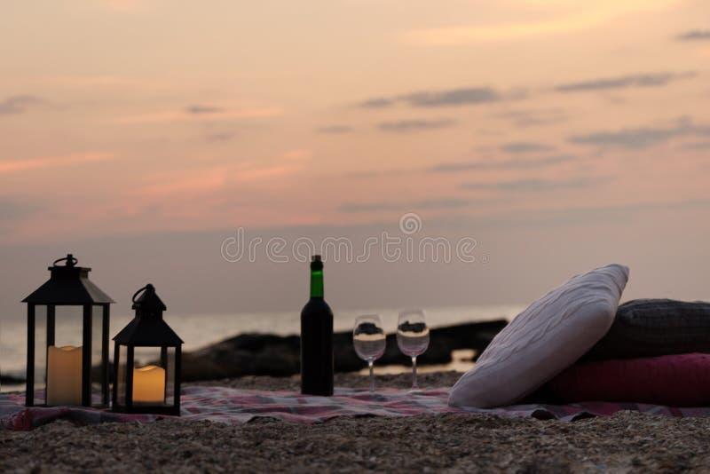 De zomer overzeese zonsondergang Romantische picknick op het strand Fles wijn, stock afbeelding