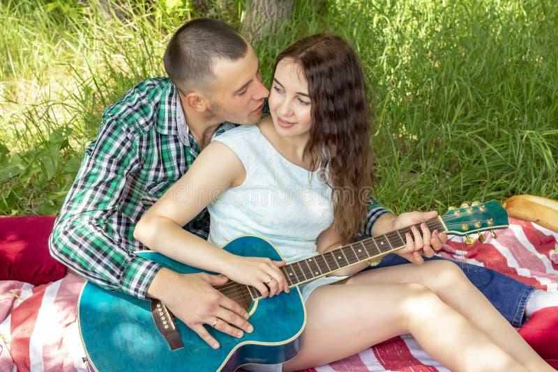 De zomer romantische picknick de kerel toont het meisje hoe te om de gitaar te spelen De zitting van het paar op het gras stock foto's