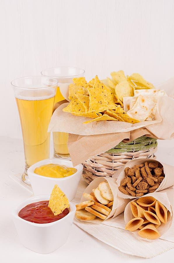 De zomer snel voedsel - verschillende knapperige snacks en rode, gele saus in witte kommen, koud bier op zachte witte houten vert royalty-vrije stock afbeeldingen