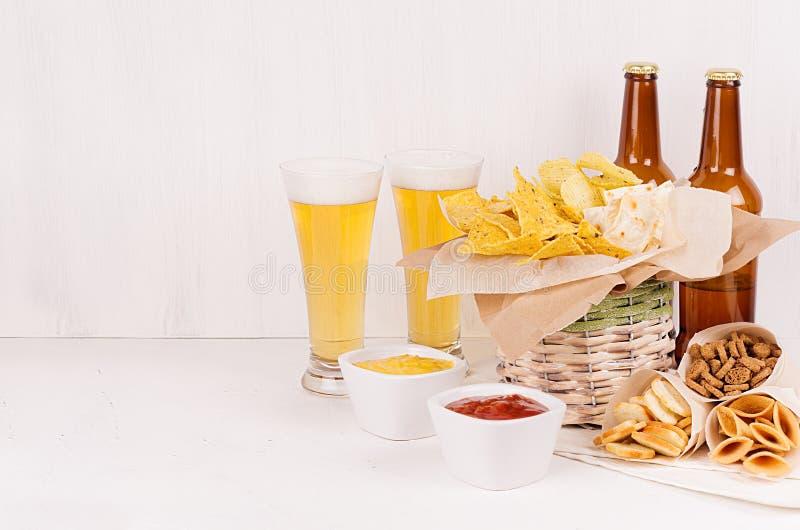 De zomer snel voedsel - verschillende knapperige snacks, twee lagerbierbier in glas en bruine flessen op zachte witte houten raad stock afbeelding