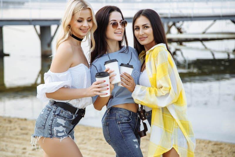 De zomer, vakantie, vakantie, gelukkig mensenconcept - mooie tieners of jonge vrouwen die pret op het strand hebben royalty-vrije stock afbeelding