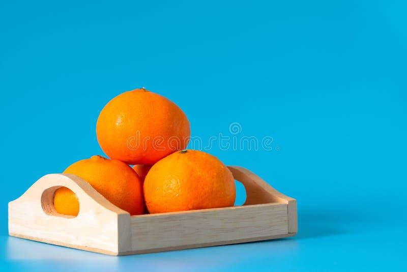 De zomer van oranje fruit in houten doos op blauwe achtergrond stock foto's