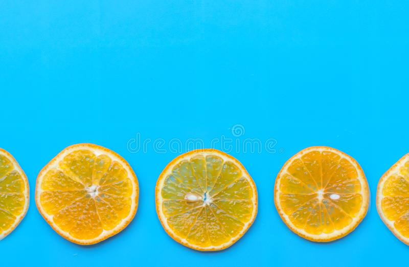 De zomer van plak oranje fruit op blauwe achtergrond stock foto