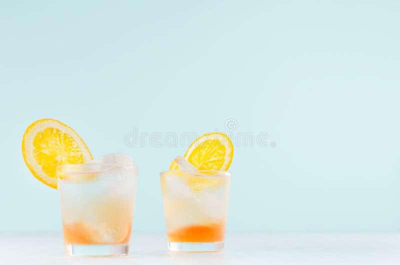 De zomer verse alcoholische dranken met sinaasappelenalcoholische drank, ijsblokjes in geschoten glas op blauwe muur, exemplaarru stock fotografie