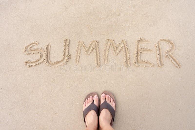 De zomer wordt geschreven op het zand van het overzeese strand Is een seizoen van rust en de reismensen laten van dit gevoel gaan stock foto