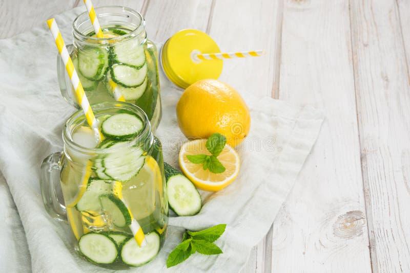 De zomer zoet water detox met citroen, komkommer, ijs en munt in metselaarkruik op een witte houten achtergrond rustic royalty-vrije stock afbeelding