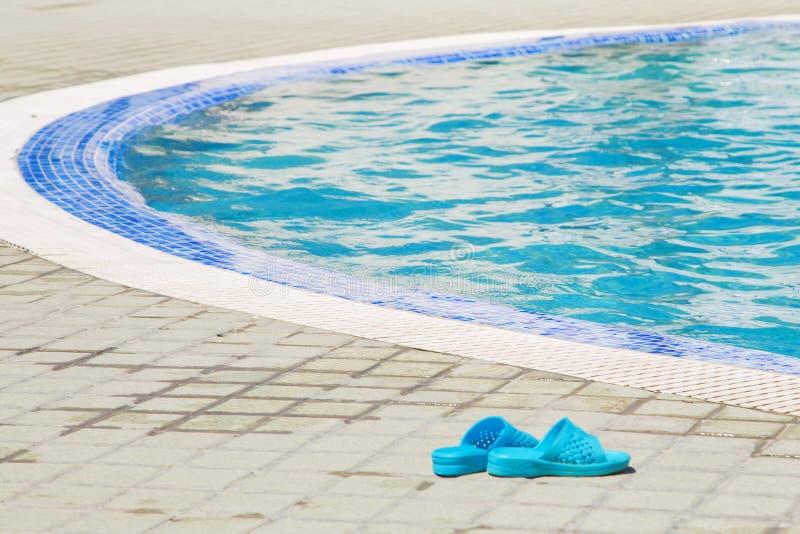 De zomerachtergrond Blauwe sandals door een zwembad stock foto