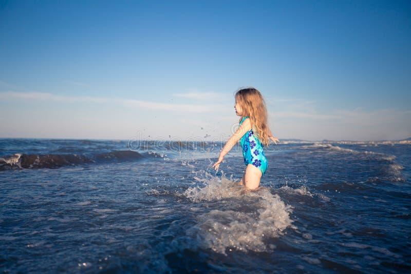 De zomerachtergrond Meisje in blauw zwempak die zich in blauwe overzees bevinden Gelukkig Kind royalty-vrije stock foto